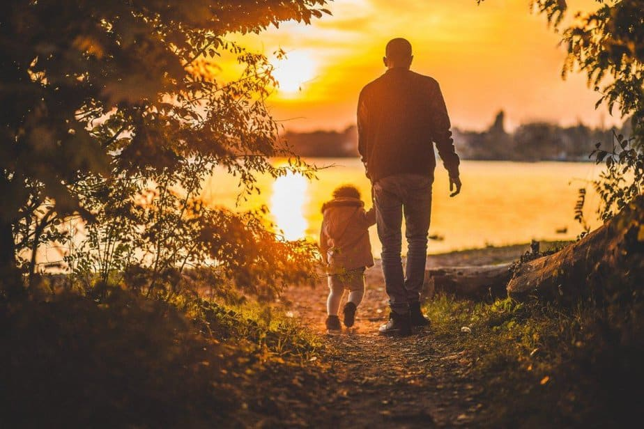 Dad and child walking in the park with sun - motherhooddiaries