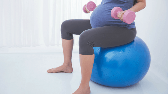 Benefits of exercise during pregnancy - pregnant woman with dumbells and swiss ball - motherhooddiaries