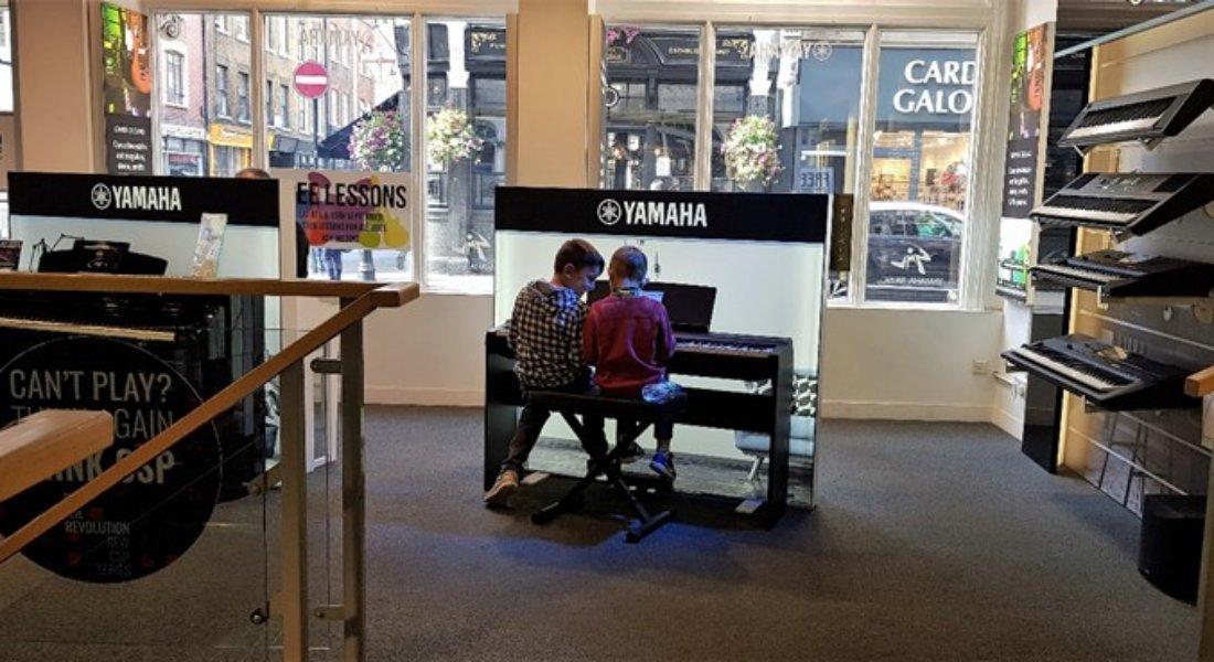 Boys playing keyboard in Yamaha Music London