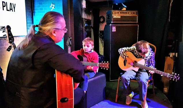 Mete teaching boys to play at Yamaha Music London store in Soho