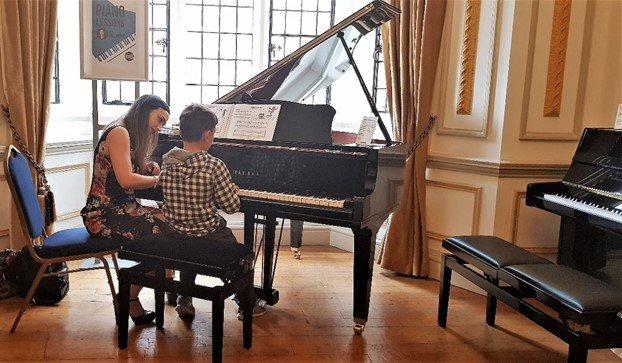 Valentina teaching Aron the grand piano at Yamaha Music London store in Soho