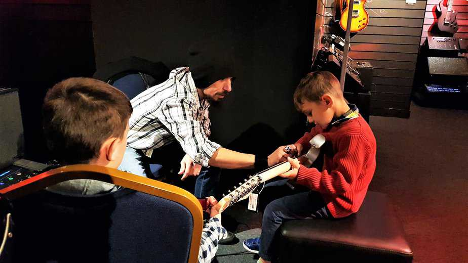 Mags showing Aidan the vibrating arm of the electric guitar at Yamaha Music London store in Soho
