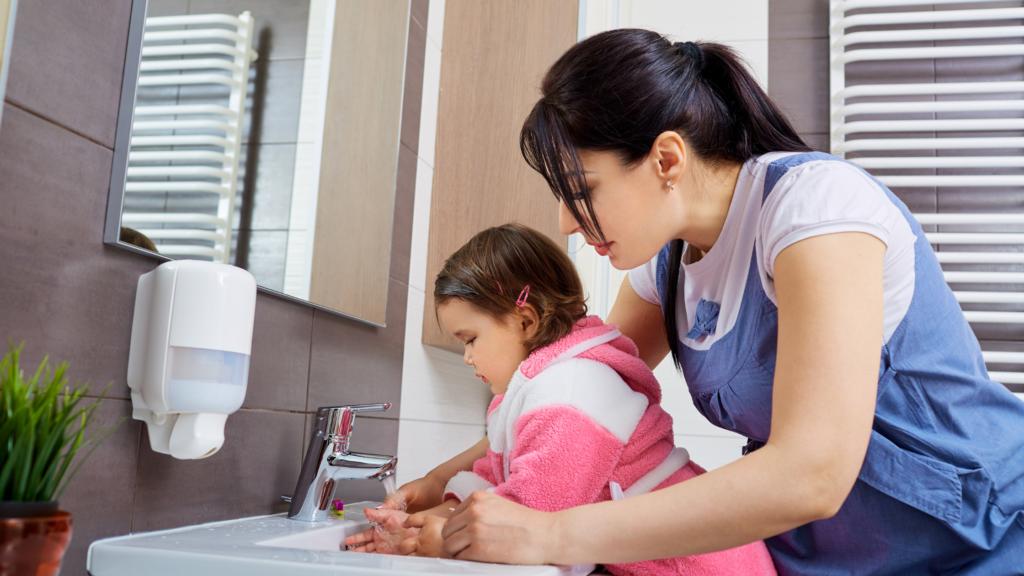 Mum helping child wash hands